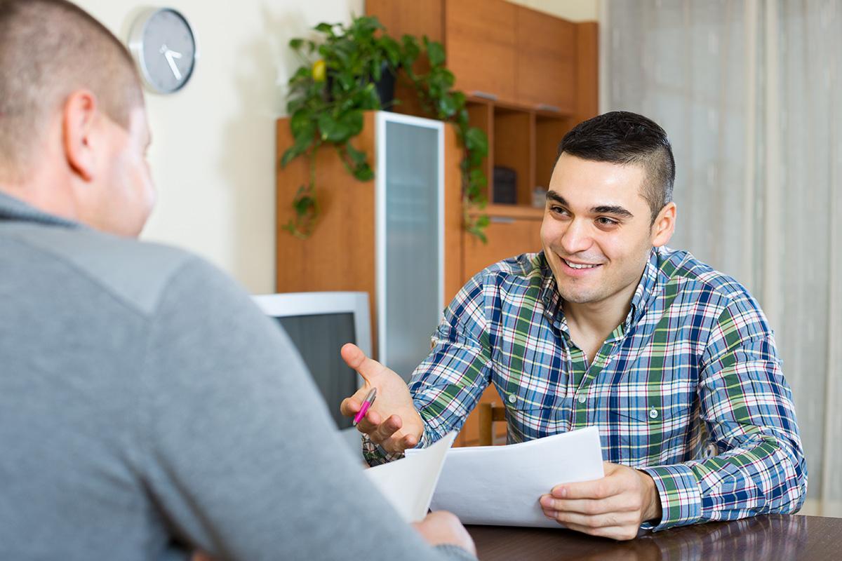 Ein Betreuer im Gespräch mit einem Menschen mit Autismus