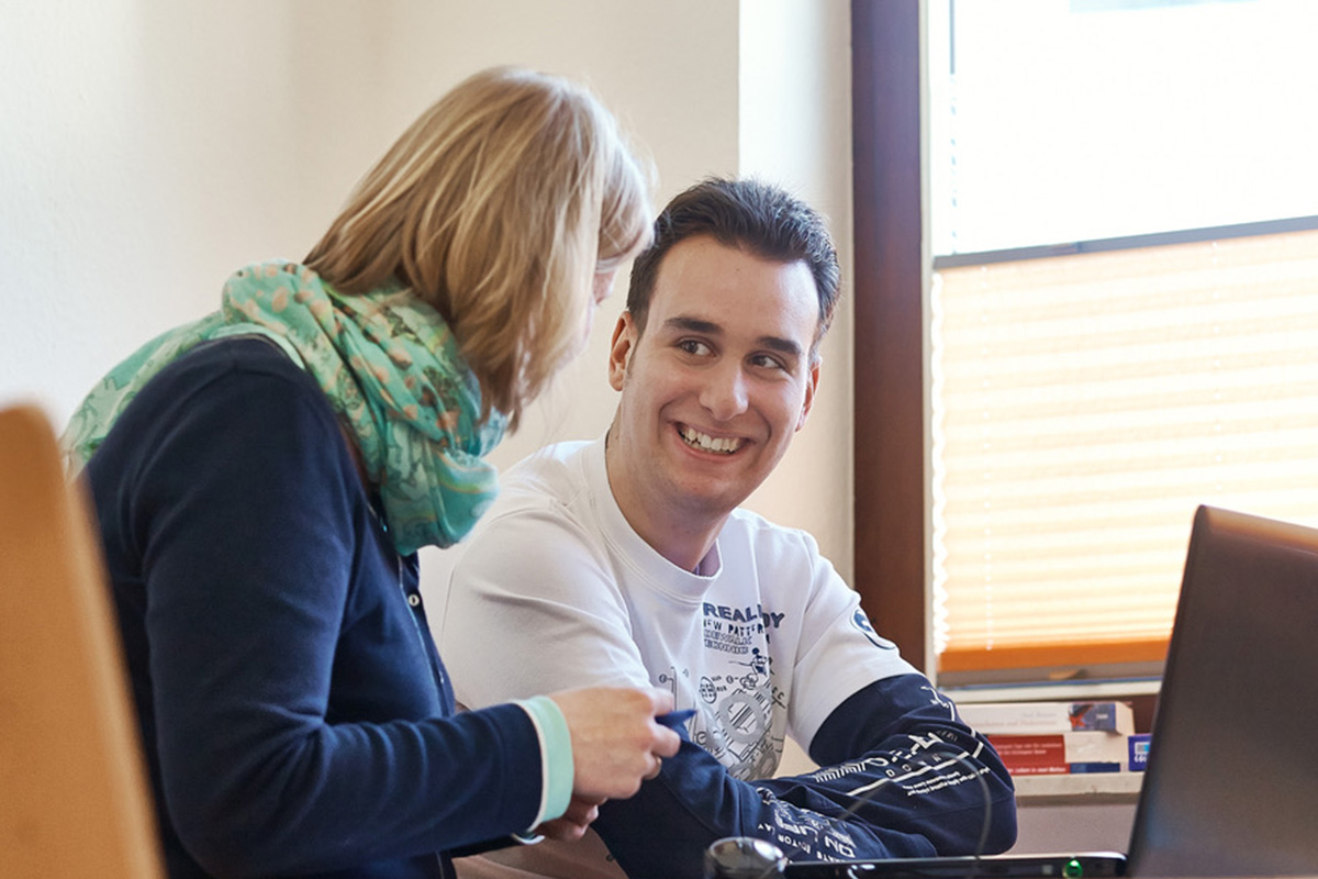 Ein Mann mit Autismus im Gespräch mit einer Therapeutin