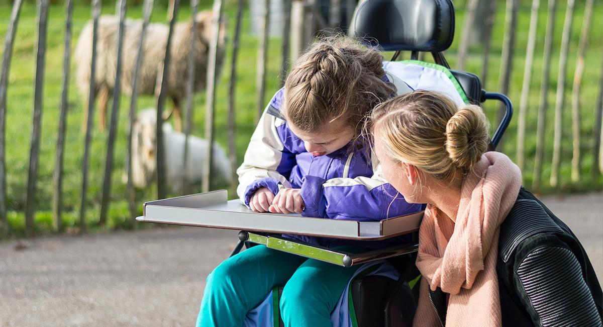 Ein Mädchen besucht mit einer Begleiterin einen Streichelzoo