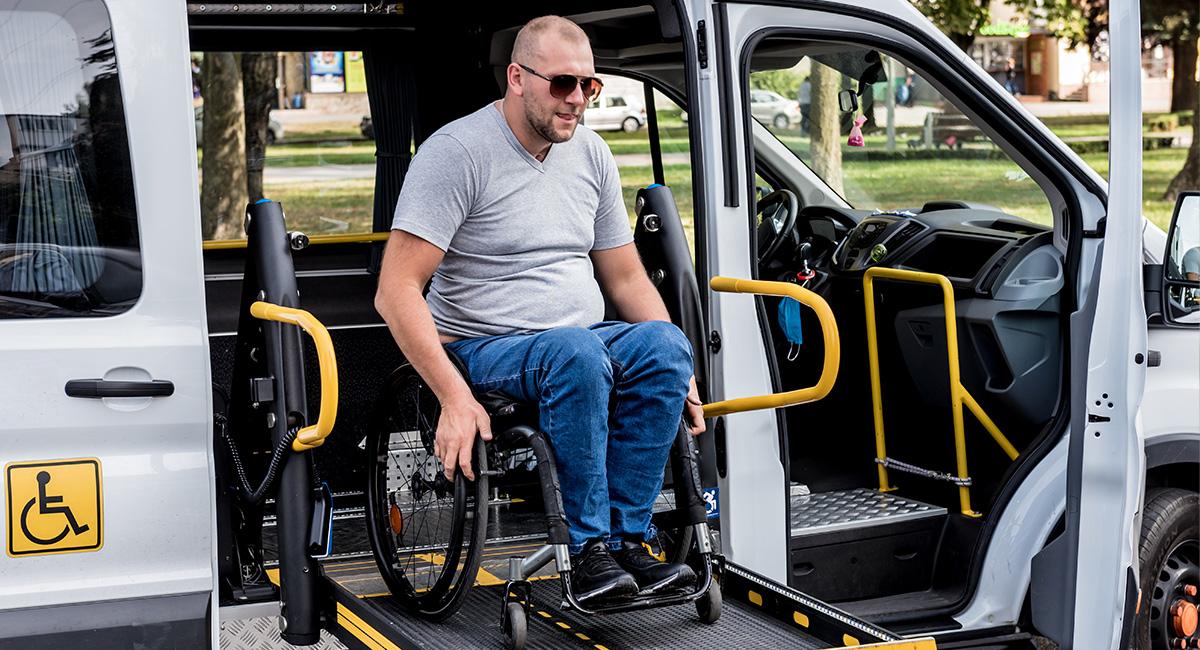Ein Mann im Rollstuhl nutzt die Hebebhüne des Fahrdienstes