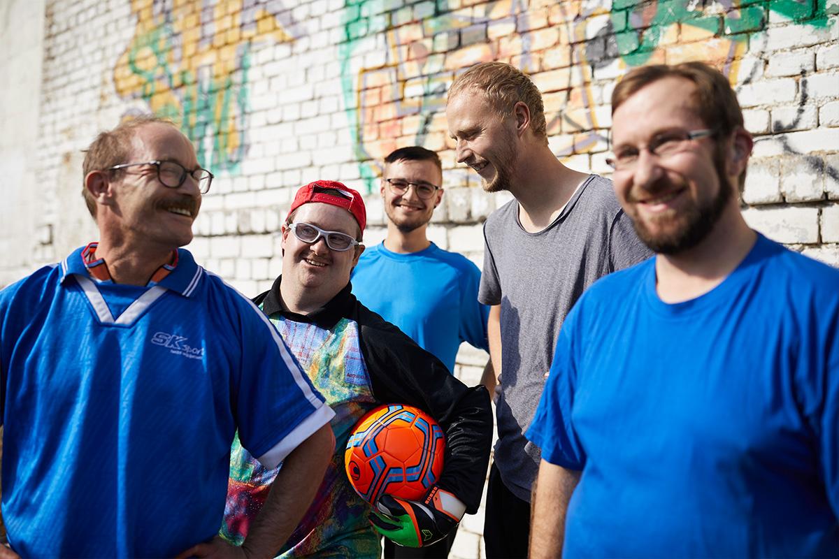 Eine Gruppe aus Männern mit und ohne Behinderung freut sich über das gemeinsame Fußballspielen