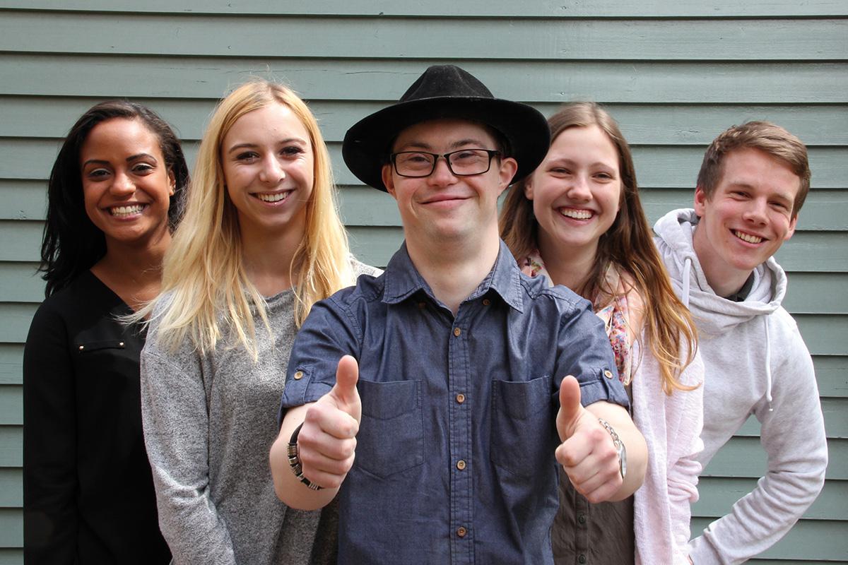 Junge Menschen lächeln in eine Kamera