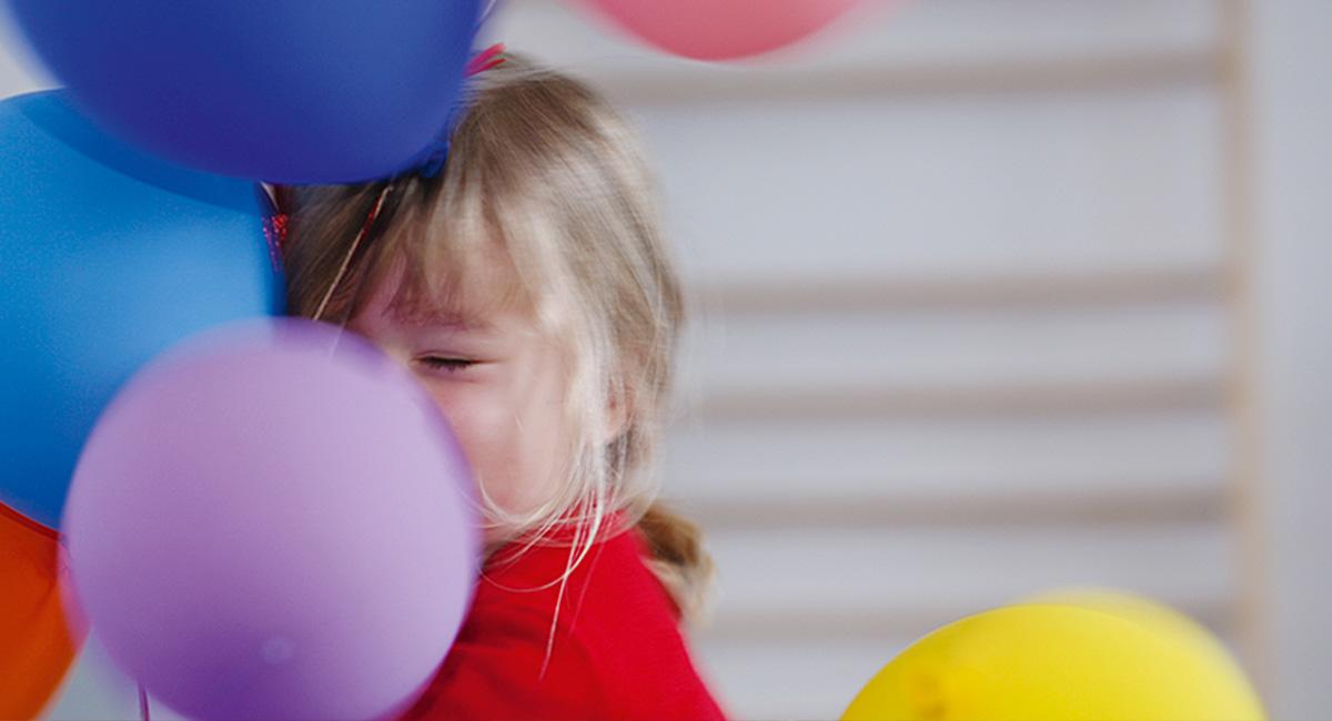 Ein Kind umarmt Luftballons