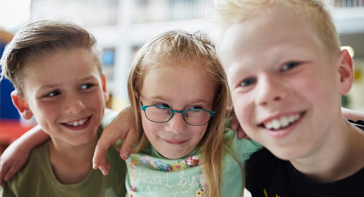 Drei Kinder lächeln in die Kamera