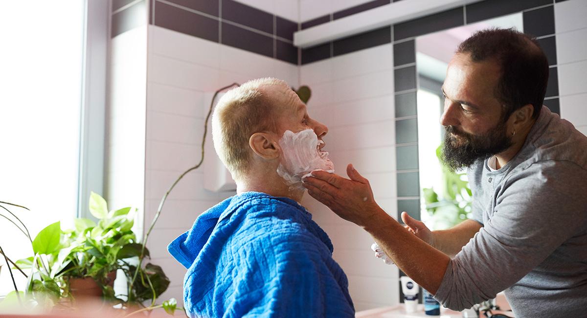 Ein Pfleger rasiert einen Mann