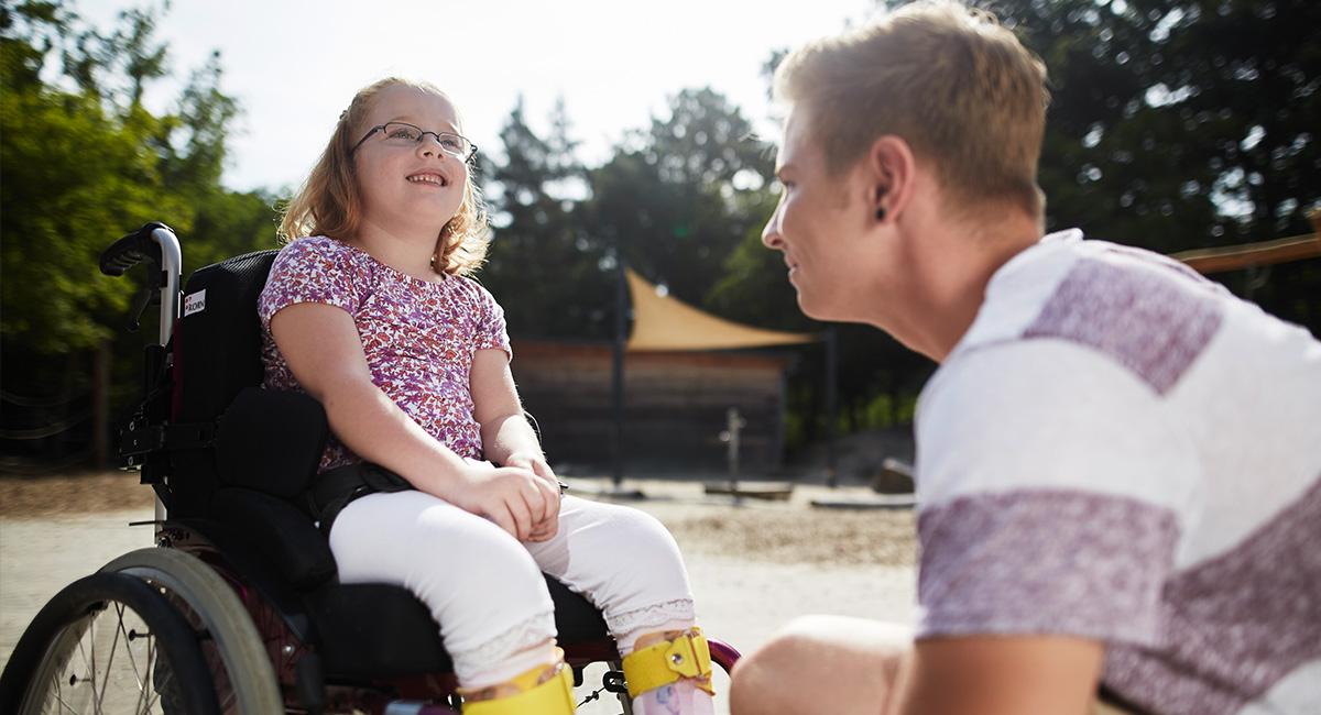 Ein Schulbegleiter mit einer Schülerin im Rollstuhl.