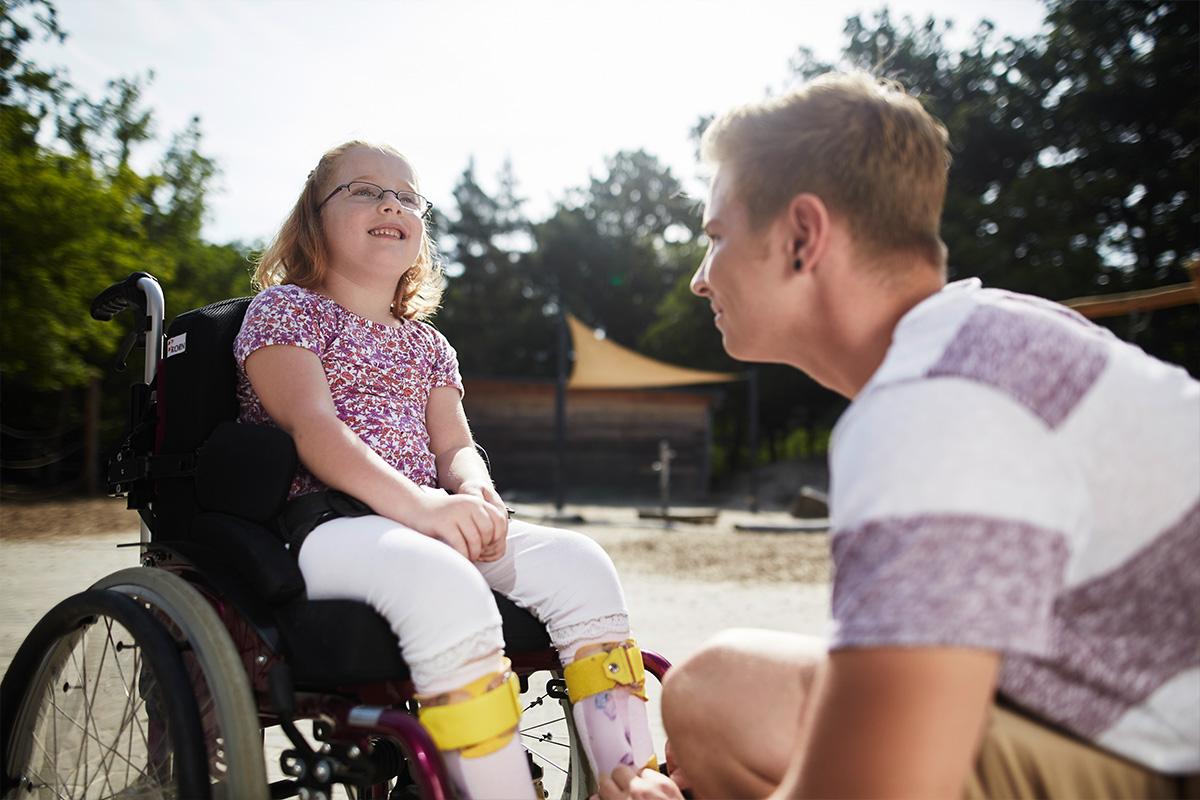 Ein Schulbegleiter mit einem Mädchen im Rollstuhl