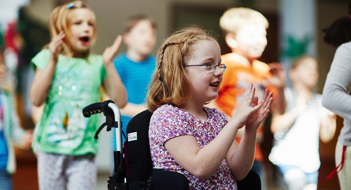 Ein Mädchen im Rollstuhl singt mit anderen Kindern im Kindergarten