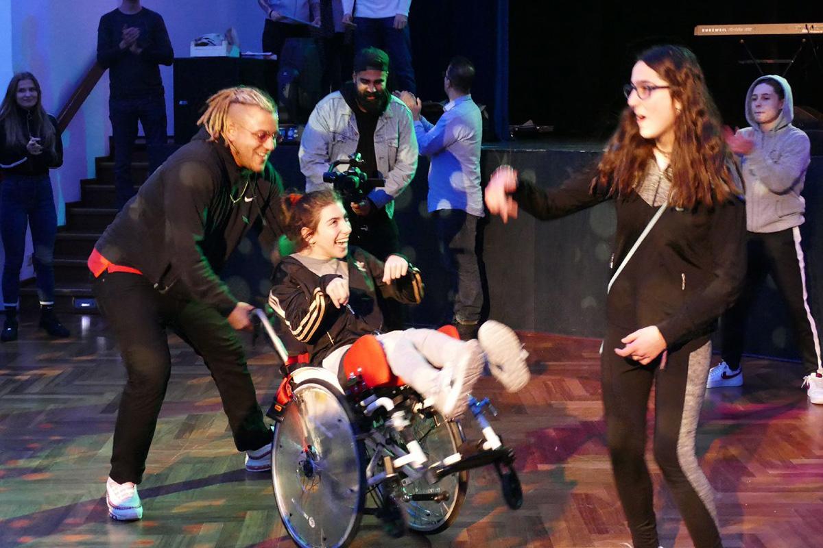 Ein Mädchen im Rollstuhl tanzt mit ihrer Freundin