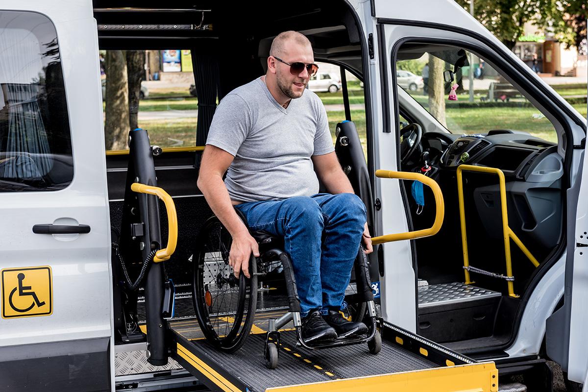 Ein Mann im Rollstuhl nutzt die Rampe eines Fahrzeuges