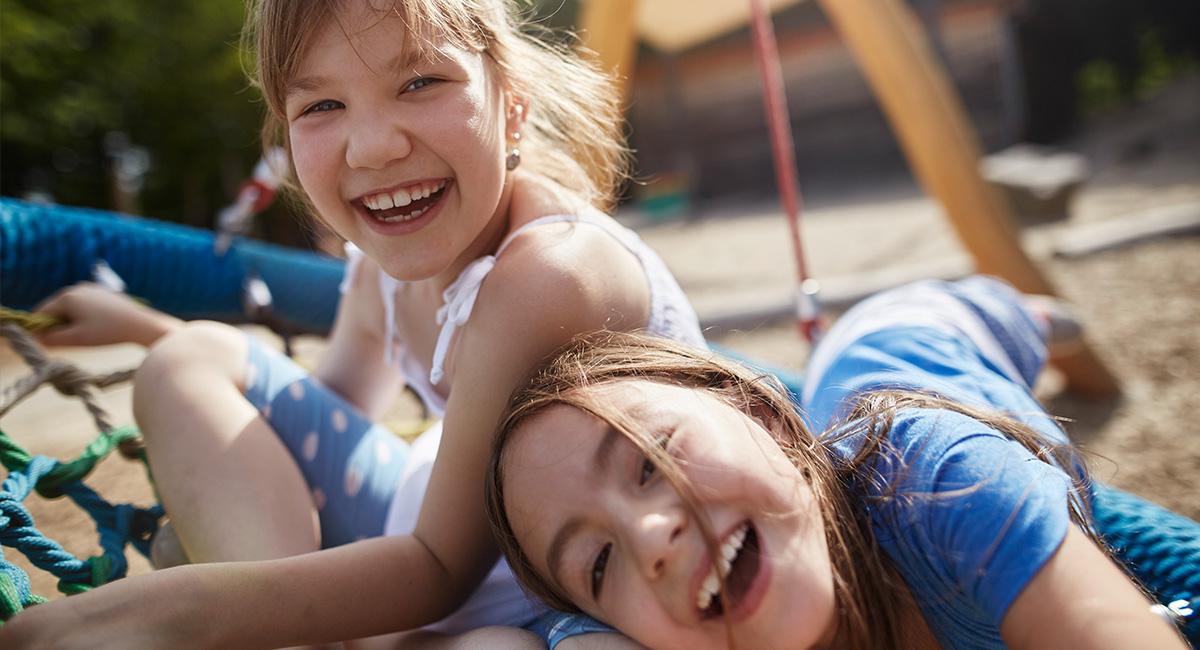 Zwei Mädchen sitzen auf einer Nestschaukel