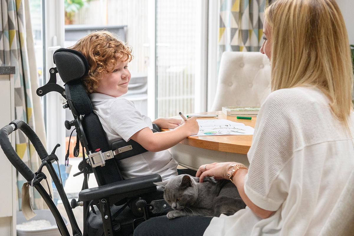 Ein Kind mit Behinderung sitzt am Tisch und malt