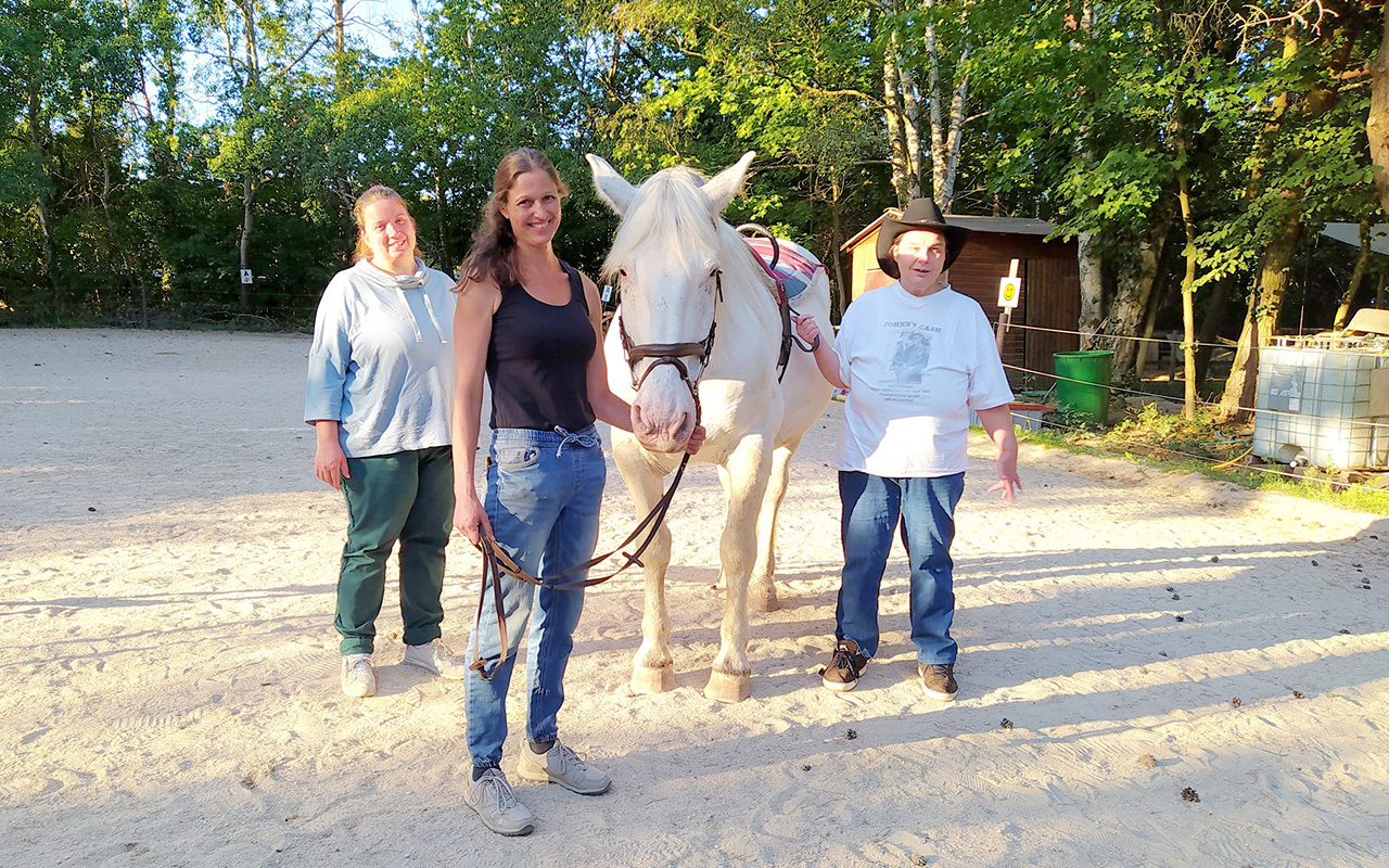 Eine Frau und zwei Menshen mit Behinderung bei der Reittherapie